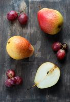 Fresh red pears and grapes on dark wooden table by BeKaphoto