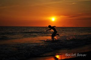 Surfin' under a golden sunset by ezleih