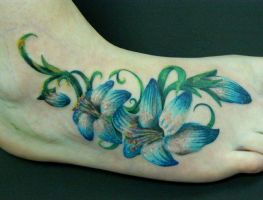 Flowers on foot tattoo by mutinytattoouk