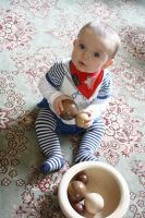 baby playing with wooden balls and a dish by U140