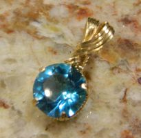 Faceted blue gem in gold by DPBJewelry