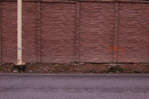 Textured Brick Wall with Pole by happeningstock