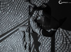 Pole dance in the light and shadows by Calabarte